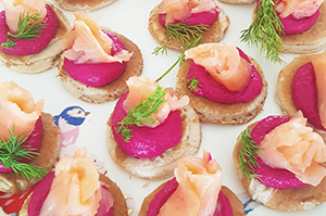 Buckwheat blinis with beetroot and feta pâté, smoked salmon ribbons and dill